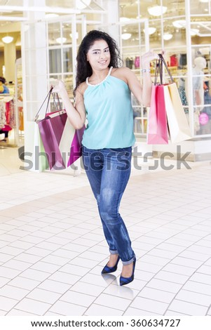 Full length of young indian woman standing in the shopping center while holding shopping bags - stock photo