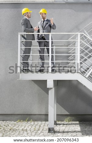 Full length of young male architects communicating on stairway - stock photo