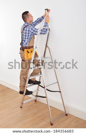 Full length of young male foreman on ladder hammering wall with nail - stock photo