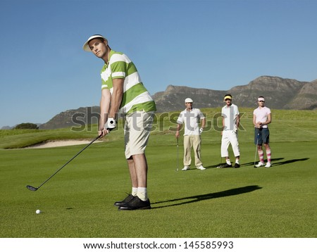 Full length of young male golfer playing golf with competitors in background - stock photo