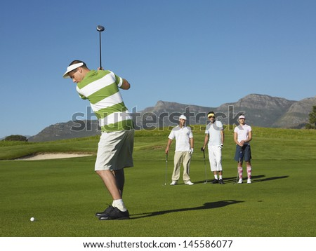 Full length of young male golfer teeing off with competitors in background - stock photo