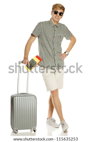 Full length of young male tourist standing with suitcase, holding tickets and passport, isolated on white background - stock photo