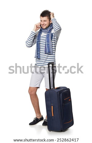 Full length of young male tourist standing with travel suitcase, isolated on white background - stock photo