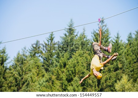 Full length of young man hanging upside down on zip line against trees in forest - stock photo