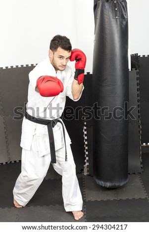 Full length of young man in kimono throwing punches  during his training - stock photo