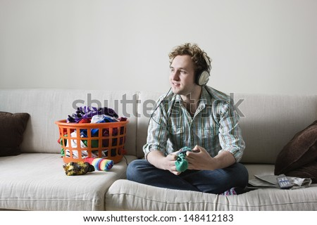 Full length of young man listening music while folding laundry on sofa - stock photo