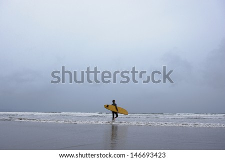 Full length of young man with surfboard walking towards sea on beach - stock photo