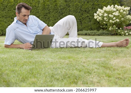 Full length of young man working on laptop in park - stock photo