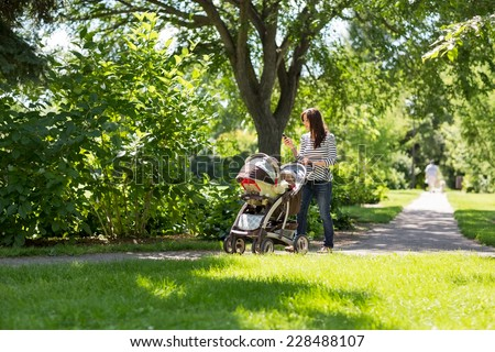 Full length of young mother pushing baby carriage in park - stock photo
