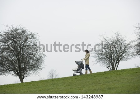 Full length of young mother pushing stroller in park - stock photo