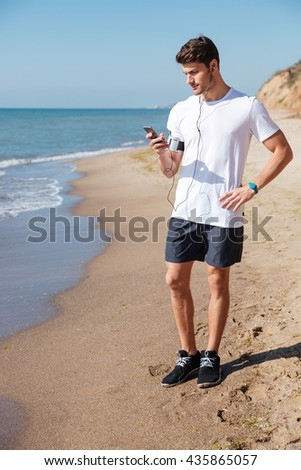 Full length of young sportsman with earphones listening to music from mobile phone on the beach - stock photo