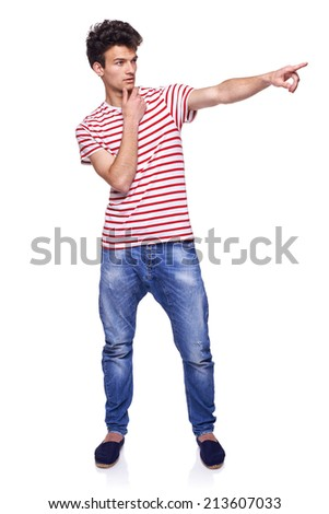 Full length of young trendy casual man pointing to the side on blank copy space, over white background - stock photo