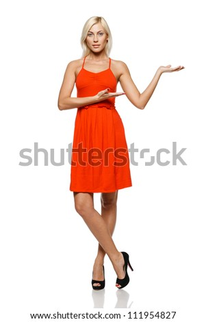 Full length of young trendy woman in bright red dress showing a product - empty copy space on the open hand palm, over white background - stock photo