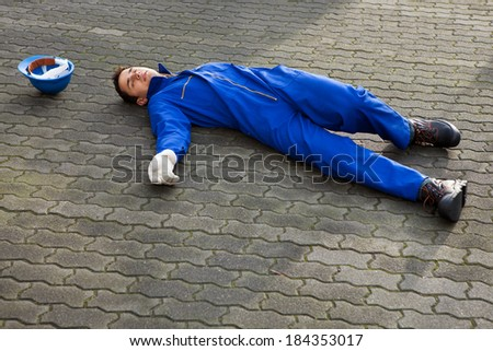 Full length of young unconscious repairman in uniform lying on street - stock photo