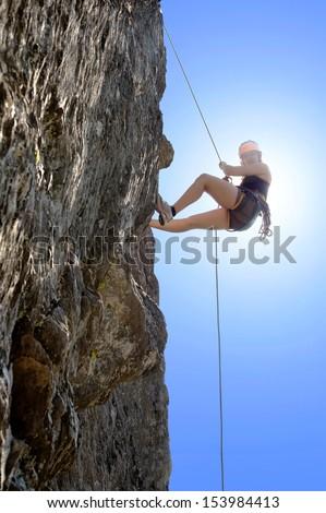 Full length of young woman climbing rock - stock photo