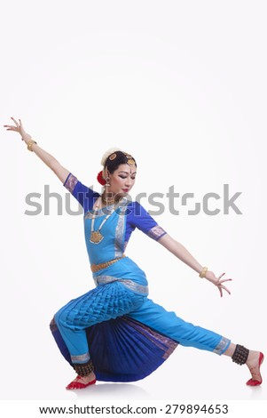 Full length of young woman performing Bharatanatyam over white background - stock photo
