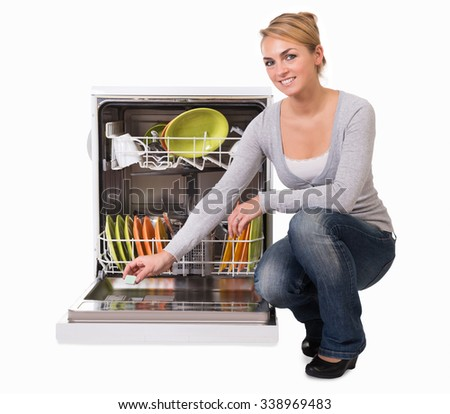 Full length of young woman placing soap in dishwasher over white background - stock photo