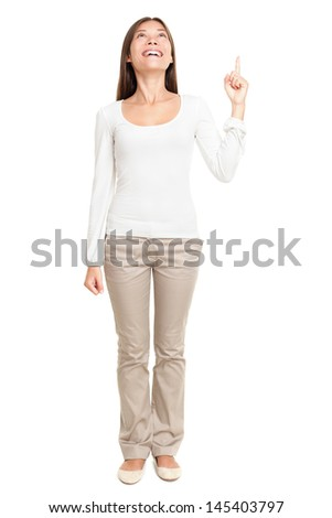 Full length of young woman pointing up at copyspace isolated over white background - stock photo
