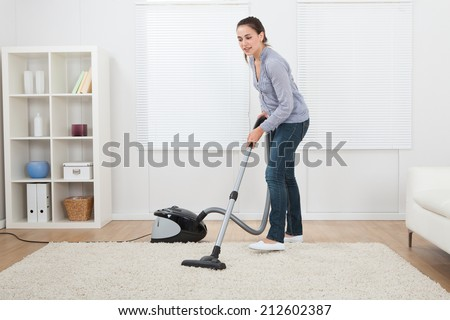 Full length of young woman vacuuming rug at home - stock photo