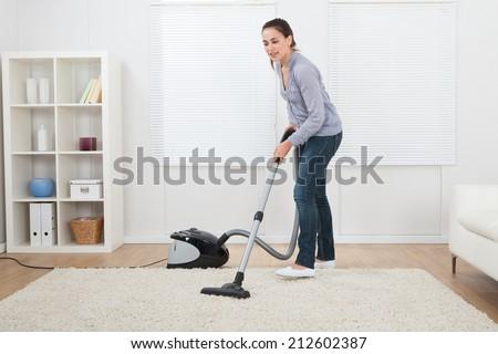Full length of young woman vacuuming rug at home - stock photo