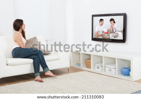 Full length of young woman watching television while sitting on sofa at home - stock photo
