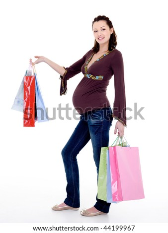 Full-length photo of a Beautiful cheerful pregnant woman with  purchases - stock photo