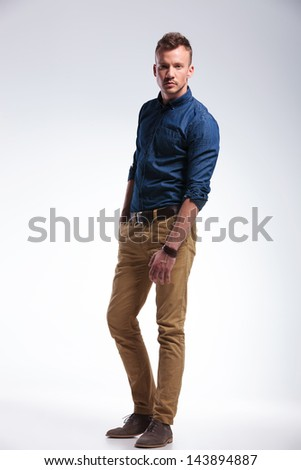 full length photo of a casual young man standing in the studio with a hand in his pocket and looking at the camera. on gray background - stock photo