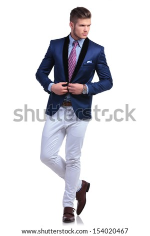 full length photo of a young business man unbuttoning the jacket of his suit while looking away from the camera. on a white background - stock photo