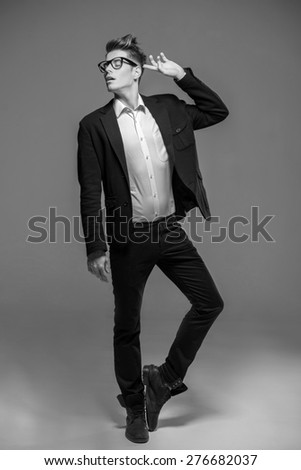 Full length photo of an elegant young fashion man in tuxedo and jeans. Black and white fashion shot. - stock photo
