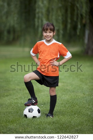 Full length photo of young girl standing with foot on soccer ball. - stock photo