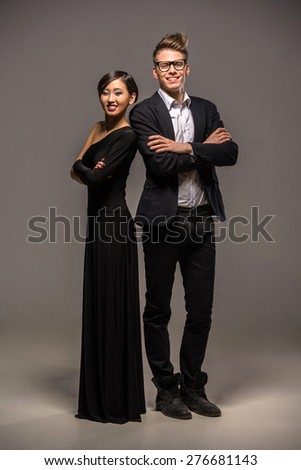 Full length photo of young  smiling couple dressed in formal clothing posing in the studio on dark background. - stock photo