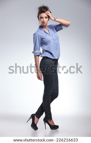 Full length picture of a beautiful fashion woman looking at the camera while fixing her hair. - stock photo