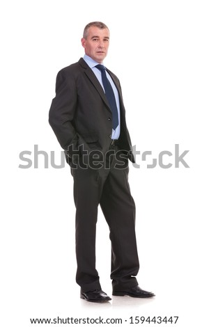 full length picture of a business man standing with his hands in his pockets and looking into the camera with a serious expression. on a white background - stock photo