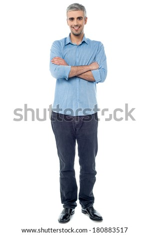 Full length picture of a casual senior man, arms folded - stock photo