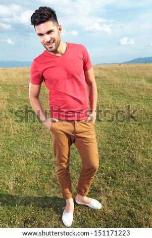 full length picture of a casual young man outdoor standing with his hands in his pockets and smiling while looking away from the camera - stock photo