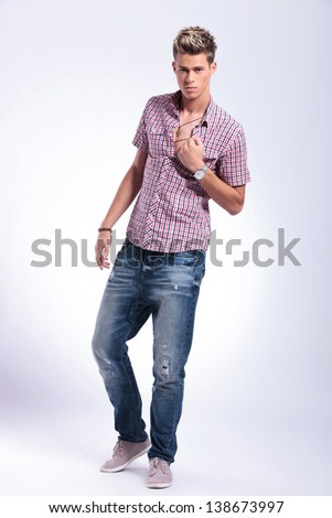 full length picture of a casual young man pulling on his shirt and revealing his chest while looking at the camera. on background - stock photo