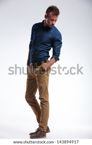 full length picture of a casual young man standing with his hands in his pockets and looking down. on gray background - stock photo
