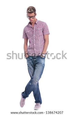 full length picture of a casual young man standing with his hands in his pockets, with his legs crossed, while looking down . on background - stock photo