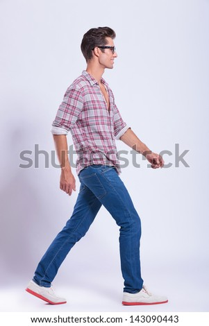 full length picture of a casual young man walking to the side of the camera and looking forward. on gray background - stock photo