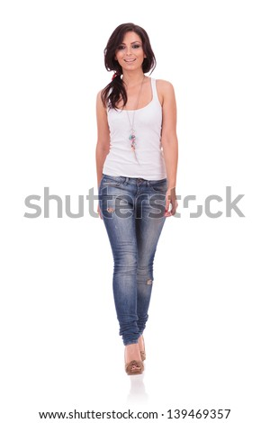 full length picture of a casual young woman walking straight toward the camera with a smile on her face. on white background - stock photo