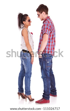 Full length picture of a cute couple standing face to face , looking at each other over white background - stock photo