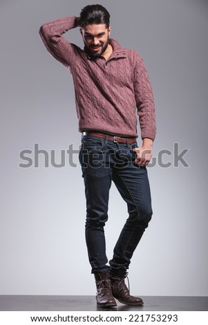 Full length picture of a fashion man wearing a red sweater, fixing his hair while holding his thumb in pocket, looking at the camera. - stock photo