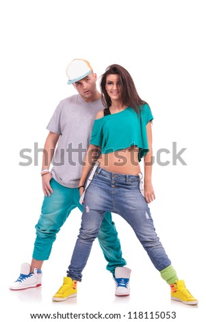 full length picture of a hip hop couple posing man behind smiling woman and looking at the camera - stock photo