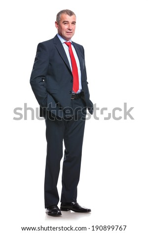 full length picture of a mid aged business man holding his hands in his pockets and looking into the camera. isolated on a white background - stock photo