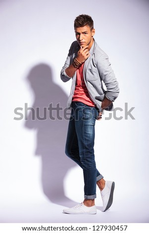 full length picture of a pensive casual young man looking at the camera and touching his chin, over light gray background with shadow - stock photo