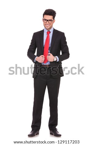 full length picture of a young business man holding his suit jacket with both hands and smiling to the camera on white background - stock photo