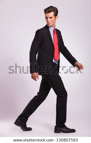 full length picture of a young business man walking forward and looking back - side view - stock photo