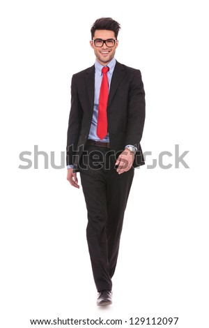 full length picture of a young business man walking towards the camera and smiling on white background - stock photo