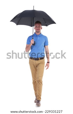 full length picture of a young casual man holding a black umbrella over his head and walking toward the camera. isolated on a white background - stock photo