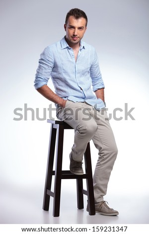 full length picture of a young casual man sitting on a chair and holding both hands in his pockets. on gray background - stock photo